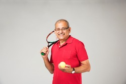 Senior indian/asian healthy sportsman playing individual sport, isolated on plain background