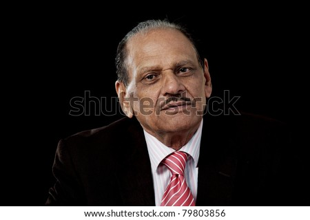 Senior indian man in business suit, horizontal portrait on black background