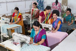 Senior inspector explaining women textile worker sewing garment on production line