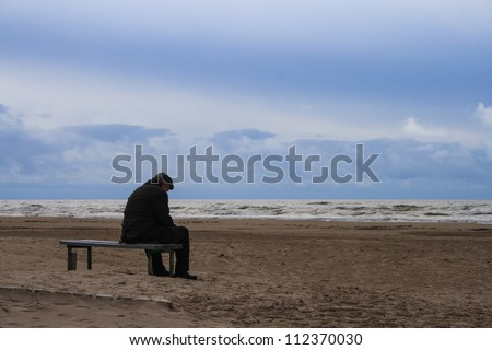 Senior is seating alone on the beach bench in overcast weather