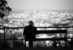 Senior is sitting alone on the bench looking at city at evening. A lonely old man sitting on a bench in a park.Elderly gentleman on park bench in contemplation,black and white photo