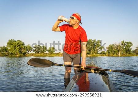 senior kayak paddler drinking water or sport drink after paddling workout on a lake in summer