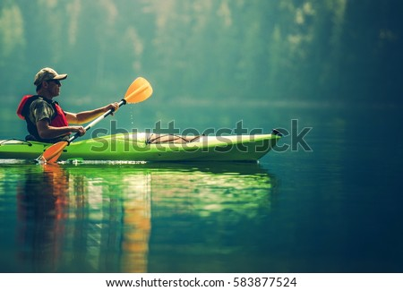 Senior Kayaker on the Lake. Kayak Paddling. Water Sport and Recreation. #583877524