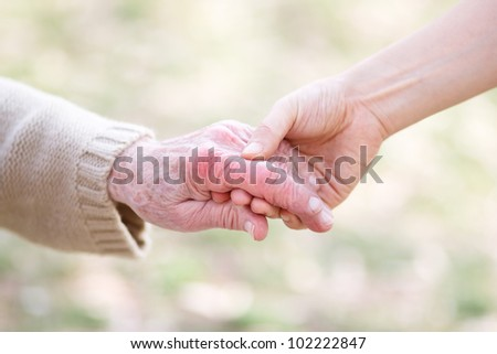 Senior lady and young women holding hands