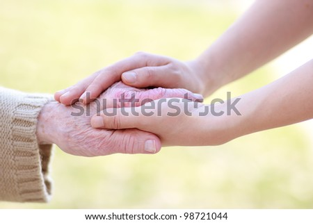 Senior lady and young women holding hands - stock photo