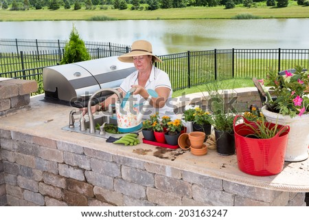 Senior lady filling a watering can at a sink in a summer kitchen on an outdoor patio to water her collection of potted plants and houseplants standing ready on the counter with a lake backdrop