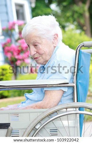 Senior lady in wheelchair outside - stock photo