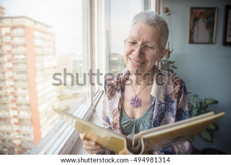 Senior lady looking at old photographs in an album, remembering her past #494981314
