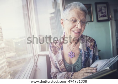 Senior lady looking at old photographs in an album, remembering her past #494981338