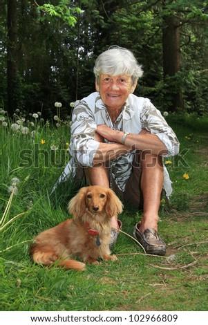 Senior lady outside with her dachshund dog. - stock photo