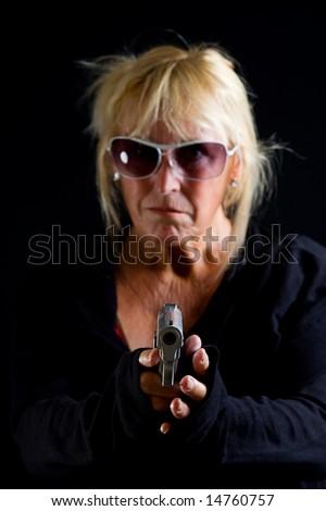 Senior Lady pointing gun towards camera against Black Background ...