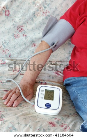 senior lady self checking her blood pressure at home
