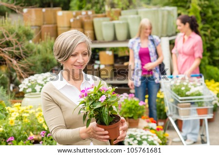 Senior lady shopping for flowers at garden center smiling