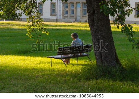 senior lady sitting on park bench in historical city in south germany near area of stuttgart