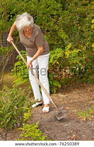 Senior lady trying to keep her garden in order