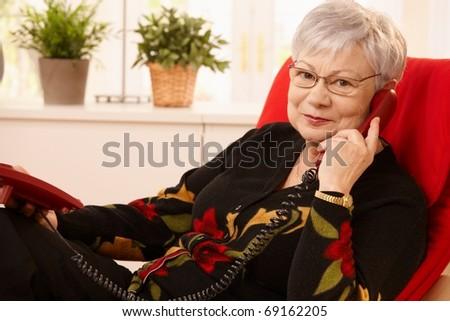 Senior lady using landline phone, sitting in living room armchair, looking at camera.?