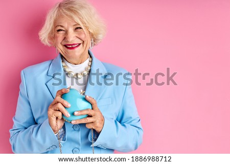 senior lady with purse in hands, caucasian female in blue blouse isolated over pink background Stockfoto ©