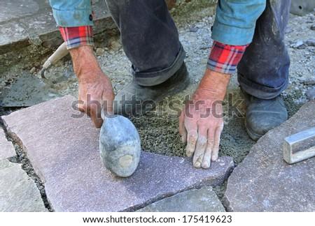senior landscape gardener fitting a flagstone tile with a rubber mallet..