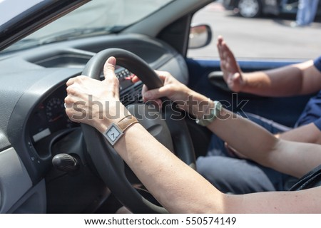 Senior learning to drive a car with a driving instructor. #550574149