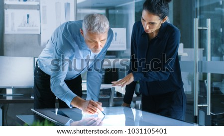 Senior Male and Young Female Architectural Designers Draw Building Concept on a Graphics Tablet Display Vertical Touchscreen Table. They Use Gestures for Zooming Project Model. #1031105401