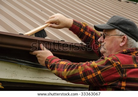 senior male cleaning out the shed gutter with brush