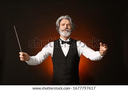 Senior male conductor on dark background