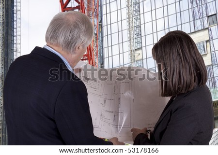 Senior male contractor and female architect look at building plans