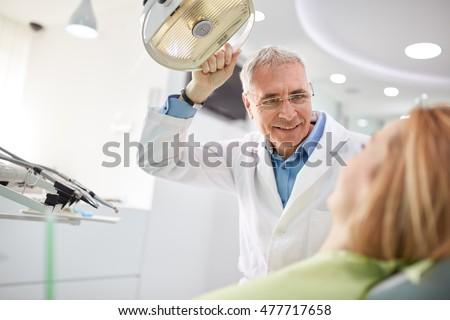 Senior male dentist adjust searchlight before starting work