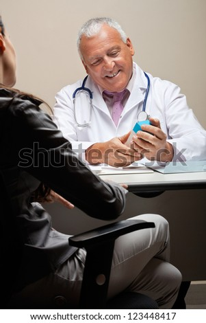 Senior male doctor holding medicine box while female patient sitting on chair - stock photo