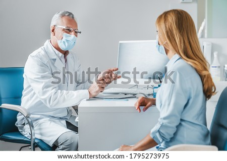 Senior male doctor wear protection face mask talking with patient in clinic office
