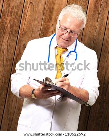 Senior Male Doctor Writing On Clipboard On Wood