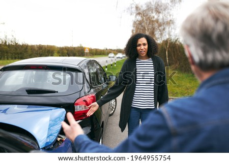 Senior male driver arguing over blame for car accident with a younger female motorist Сток-фото ©