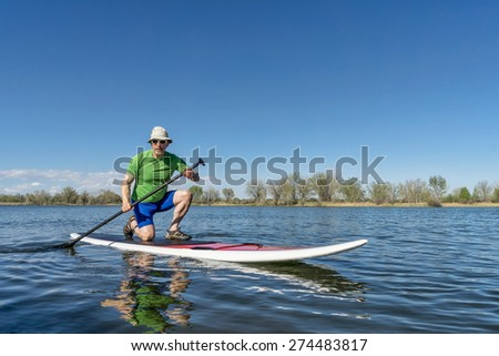Senior male exercising on stand up paddling (SUP) board. Early spring on a calm lake in Fort Collins, Colorado..