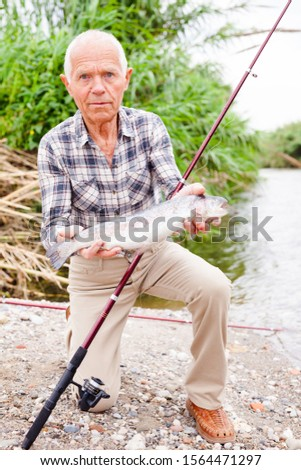 Senior male fisher examining catch fish while angling at lakeside on summer day