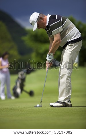 Senior male golf player putting a golf ball on the green into the hole with female golf player waiting in the background.