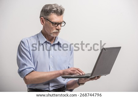 Senior male in glasses with laptop on grey background. #268744796