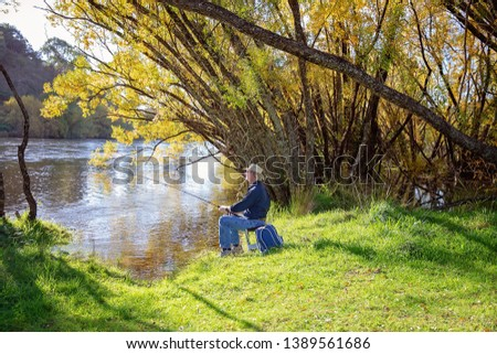 Senior male in retirement on holiday fly fishing for river trout