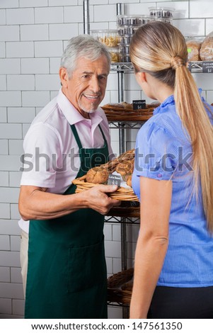 Senior male owner assisting female customer in buying muffins at supermarket - stock photo