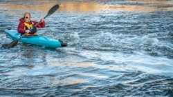 senior male paddling a whitewater kayak on a turbulent river - SOuth Platte RIver in northern Colorado