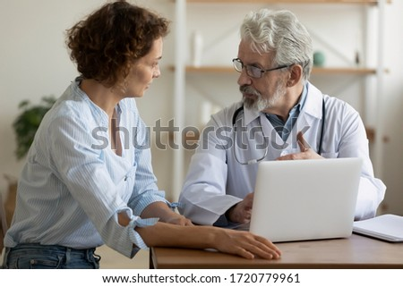 Senior male professional physician consulting female patient showing test result using laptop. Old doctor prescribe healthcare treatment talking to woman client during checkup visit in medical center.