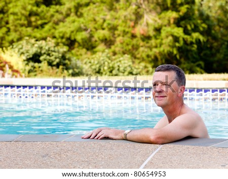 Senior male relaxing by the side of a modern swimming pool in back yard garden and facing the camera with smile