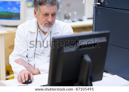senior male researcher carrying out scientific research in a lab (shallow DOF; color toned image)