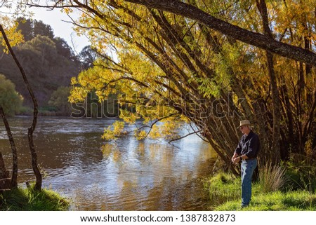 Senior male retiree on holiday fly fishing for river trout