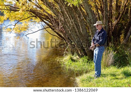 Senior male retiree on vacation fly fishing for trout in a river