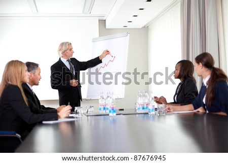 Senior male speaker giving presentation at a business meeting
