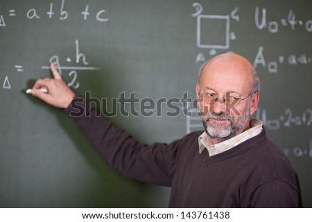 Senior male teacher teaching mathematics while pointing at blackboard in classroom