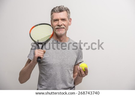 Senior male trainer with tennis racket and tennis. Foto stock ©