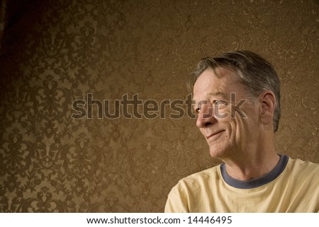 Senior Man Against a Gold Background Looking Left