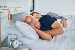 Senior man and mature woman sleeping together in their bed. Married middle aged couple resting with eyes closed in the morning. Wife lying on side embracing her husband while dreaming.