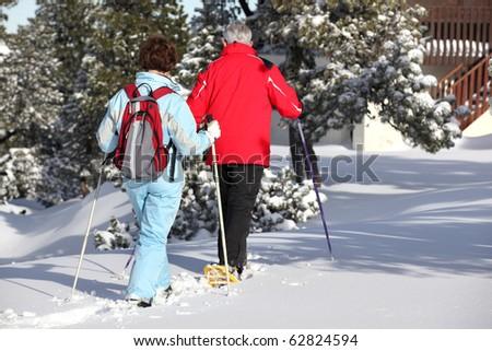 Senior man and senior woman snowshoeing back to snow